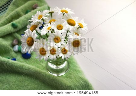 Beautiful background with flowers and a green towel. Daisies on white.