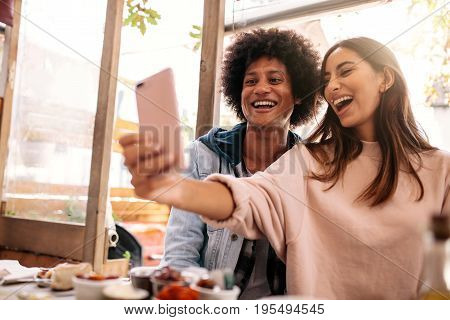 Young couple sitting in the cafe and taking selfie with smart phone. Beautiful woman taking self portrait with her boyfriend in restaurant.