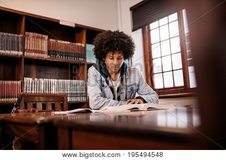 African college student reading book in library. Young student sitting at table in library and studying.