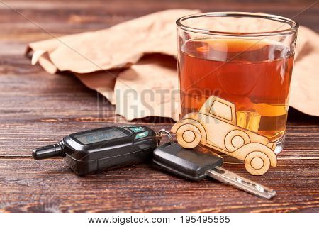 Car, whisky, automobile keys. Brandy with ice, car, automobile keys on wooden background. Concept of drunk drivers accidents.