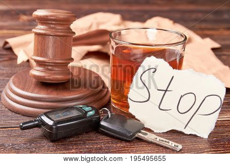 Gavel, car keys, glass of alcohol. Whiskey glass, message stop, car keys, gavel on wooden background. Forbidden alcohol drinking and driving.