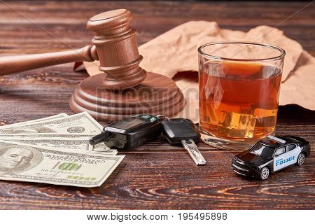The concept of drink driving. Amount of money, car keys, gavel, whiskey, police car on wooden background. Money penalty for drunk drivers.