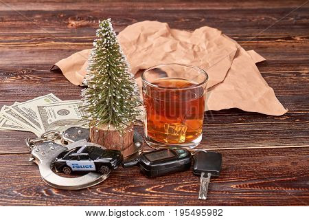 Keys, handcuffs, alcohol, new year tree. Police car in handcuffs, driving keys, whiskey, american money on wooden background.