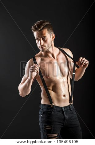 Sexy Muscular Shirtless Man In Suspenders On Dark Background