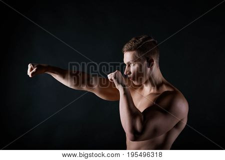 Profile portrait of strong young European sportsman with naked muscular torso boxing punching air in front of him. Attractive shirtless male boxer or kickboxer exercising in gym. Martial arts concept