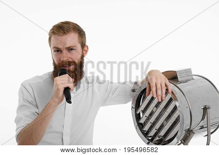 Attractive stylish unshaven young male singer or presenter holding microphone and placing hand on spotlight lamp singing a song or presenting something. People music and entertainment concept