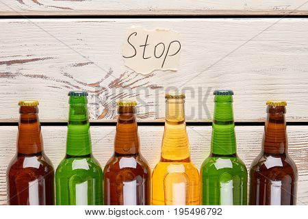 Inscription stop above glass bottles. Stop drink alcohol and save your life.