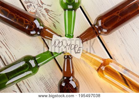 Top view of message and bottles. Colorful glass bottles with inscription no more.