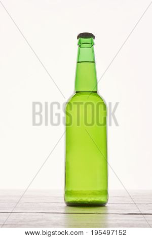 Single bottle of lager isolated. Fresh cold beer, wooden table.