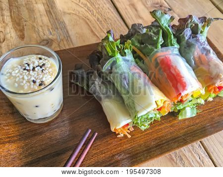 Salad roll vegetables and crab stick with salad dressing in wooden plate