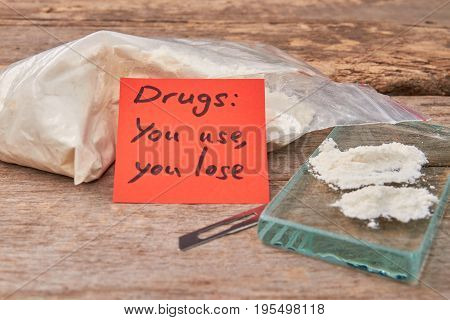 Use of drugs leads to death. Narcotics, glass, message, blade, wooden board.
