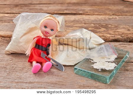 Narcotics, doll, blade, wooden background. Stop use heroin, think about future generation.