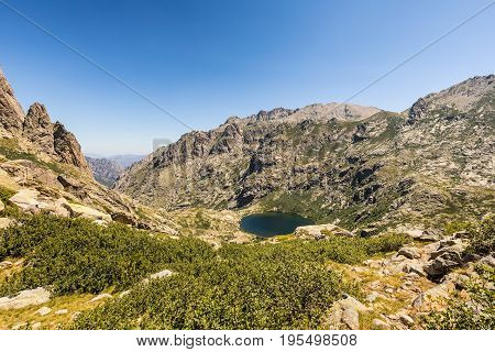 View looking down on Lac de Melo at the head of the Restonica valley near Corte in Corsica with rocks in the foreground and blue sky