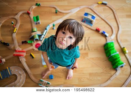 Sweet Preschool Child, Playing With Wooden Railway And Trains At Home