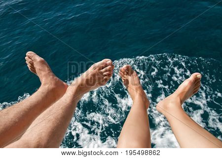 Bare feet men and women over the sea on a yacht