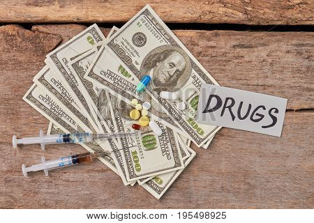 Save health and money from drugs. Doping, money, old wooden background.