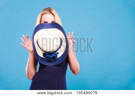 Summer trendy fashionable outfit ideas concept. Blonde attractive woman wearing short blue cocktail dress holding sun hat