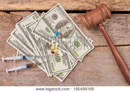 Syringes, money, pills, gavel. Law against use of drugs.