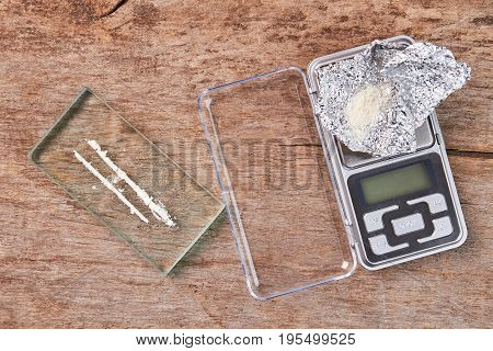 Narcotics, digital scales, wooden background. White powder, glass, scale, foil, old wooden floor.