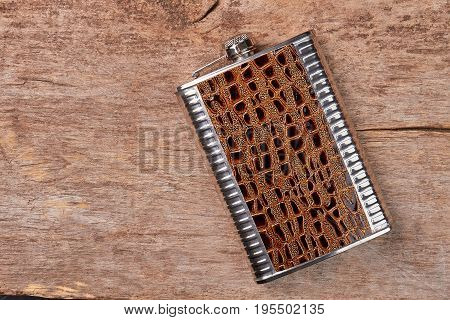 Stylish brown hip flask, wooden background. Steel jhip flask as souvenir.