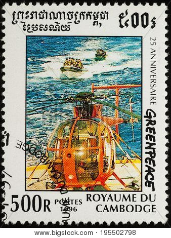 Moscow Russia - July 15 2017: A stamp printed in Cambodia shows the helicopter stands on the deck of the ship motor boats in the sea series
