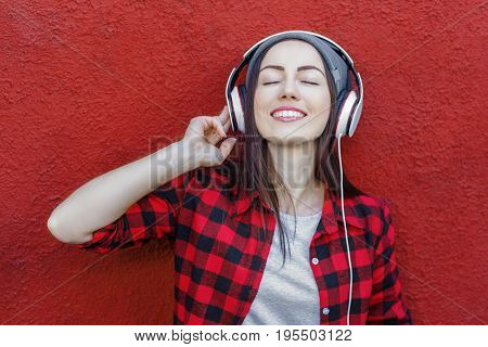 Portrait of happy hipster woman listening music in headphones. Technology, music, lifestyle and millennial people concept