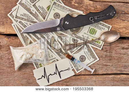 Drugs, dollars, knife, spoon, syringe. Narcotics addiction and drugs trafficking.