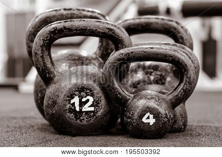 Kettlebell. Five old and rusty Kettlebells on the floor. With film grain.
