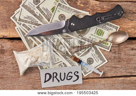 Money, drugs, spoon, knife, message. Amount of money, hard narcotics, knife, vintage spoon, syringe on old wooden background.