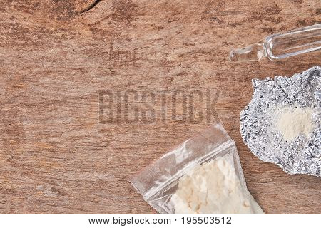 Drugs, foil, ampoule, copy space. Narcotic preparations, wooden background.