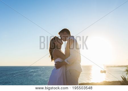 Couple embracing and kissing each other on the beach against ocean.