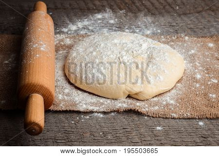 Ball of pizza dough and a rolling pin on a rustic wooden background with dusting of flour