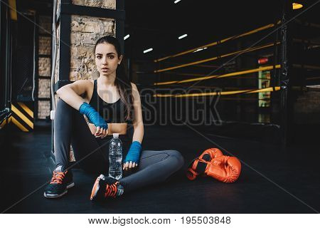 Young woman is sitting with bottle of water and red boxing gloves beside her after hard workout in the gym on the black floor.