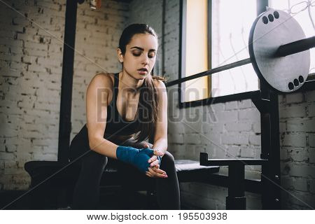 Tired attractive woman with wrapped hands with blue bandage tape for fighting sitting on the bench with closed eyes and bent head. Close up