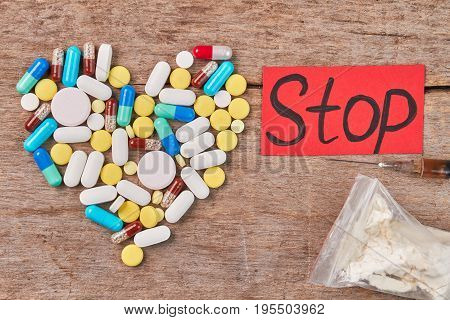 Stop use drugs how to. Pills shaped heart, narcotics, message, wooden background.