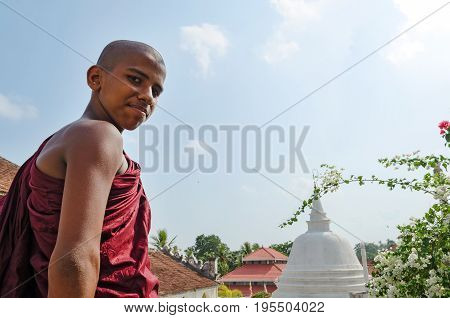 Dickwella Sri Lanka 04-15-2017: Young Buddhist monk on the background of a Buddhist pagoda looks at the camera