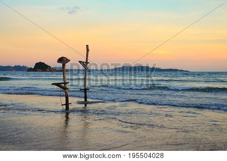 Traditional Sri Lankan poles for fishing. One of them has a hat. Beach of the ocean at sunset.