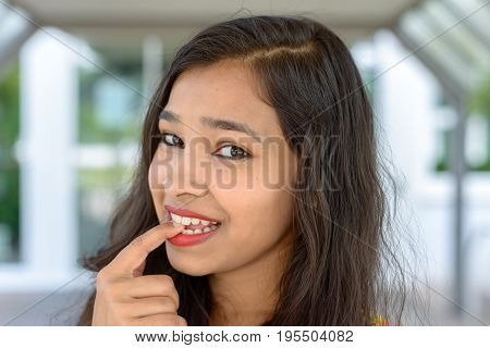 Thoughtful Young Indian Woman Biting Her Finger