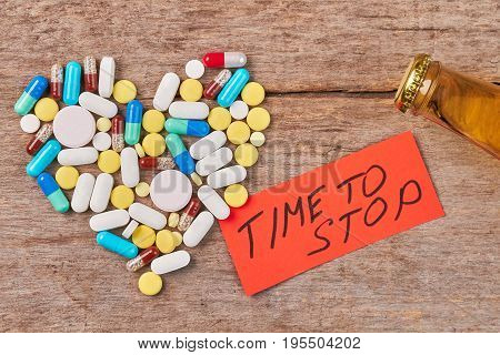 Time to stop drinking alcohol. Heart from colorful pills, message, bottle with alcohol, wooden background.