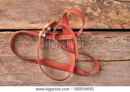 Brown tourniquet on wooden background. Medical tourniquet on old wooden surface. Tourniquet tool for blood flow stopping.