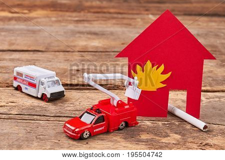 Toy ambulance, fire truck, flame. Harmful habit of smoking dangerous for life.
