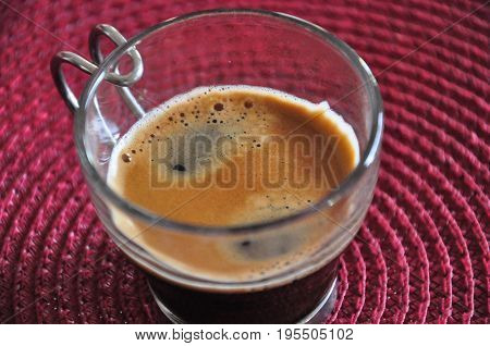 A shot of espresso on a red lined background.
