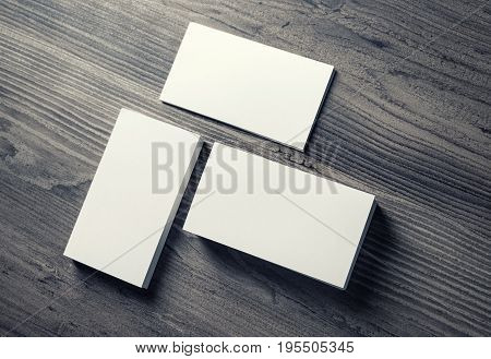 Photo of blank business cards on wooden table background. Template for ID. Mockup for branding identity. Top view.