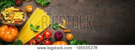 Italian food background. Uncooked Pasta tomato basil. Long banner format.