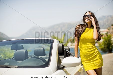 Pretty Young Woman With Mobile Phone By White Cabriolet Car
