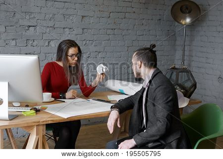 Angry female chief executive officer wearing glasses feeling mad while having intense conversation with male employee in modern office holding crumpled paper in her hand telling him to remake report