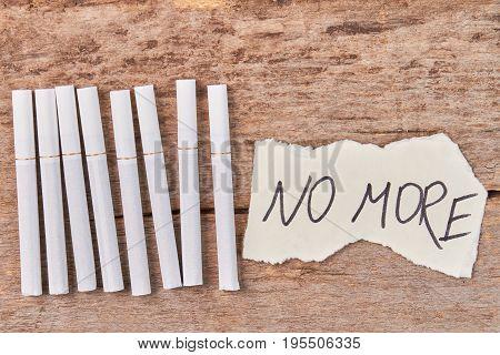 Tobacco cigarettes, message no more. White tobacco cigarettes and message lying on wooden background.