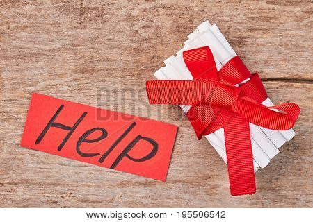Cigarettes with red ribbon and bow. Cigarettes with red ribbon, red message help, old wooden background.