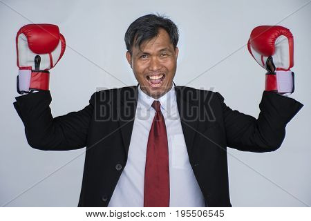 Businessman rejoice with success./Asian Businessman fighting with boxing gloves on a white background, Business competition concept