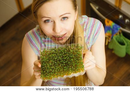 Happy woman holding green cuckooflower cress grown on cotton. Easter season decorations and food.